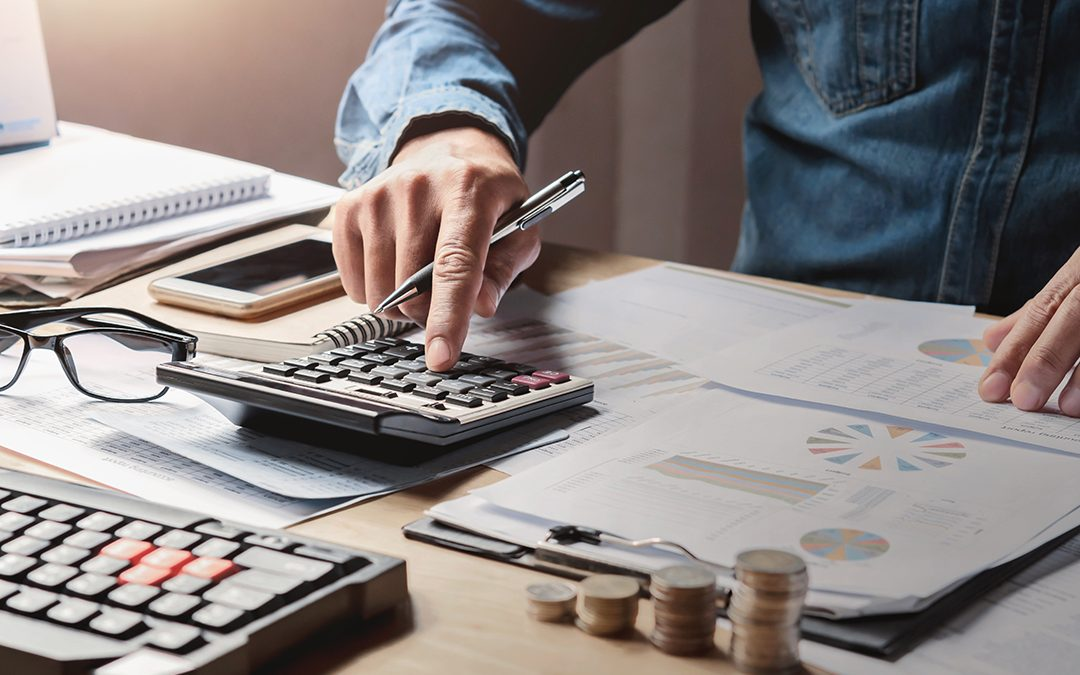 Businessman at desk working on calculator to determine cost of goods sold