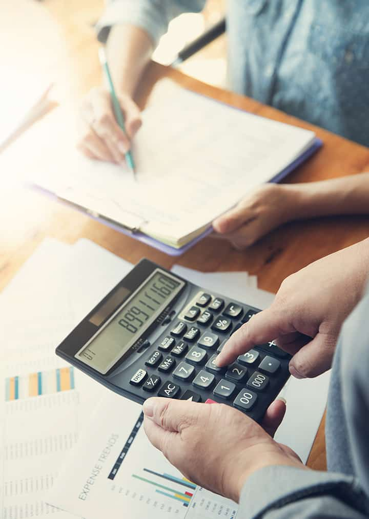 Outsourced CFO making projections for business using calculator