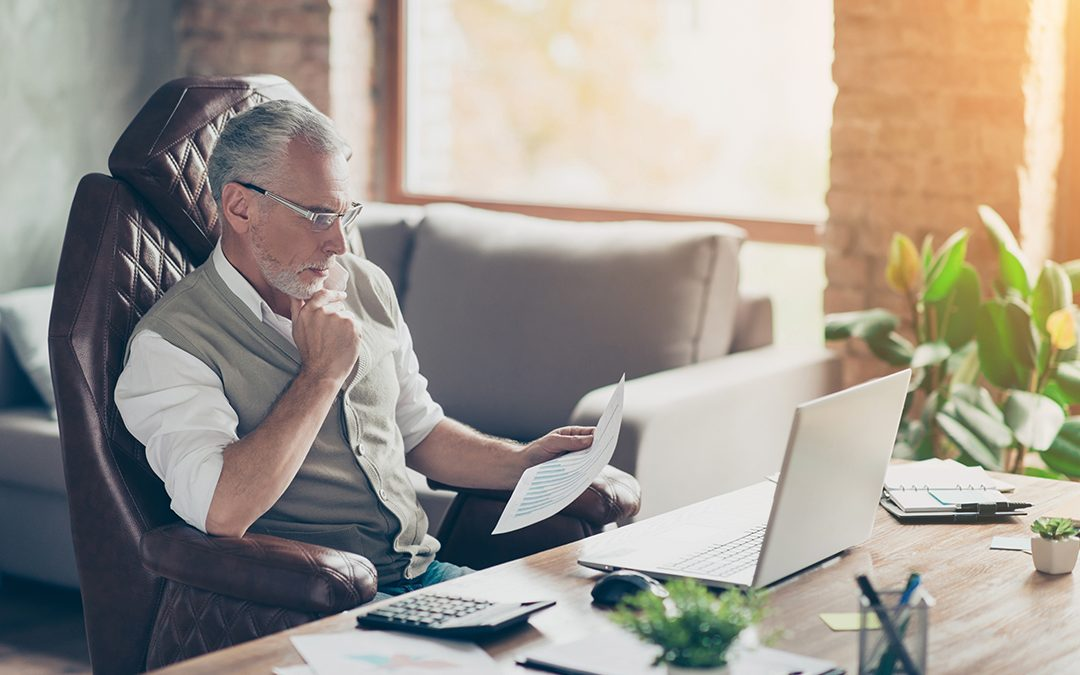 Business Man sitting in front of computer analyzing fixed vs variable costs